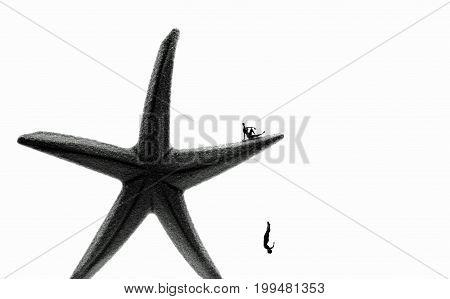 miniature man jump down a huge starfish