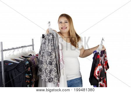 Portrait of happy overweight woman smiling at the camera while holding many clothes isolated on white background