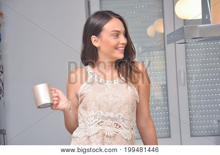 Beautiful smiling girl drink hot tea in the kitchen. Portrait of cute teenage girl drink coffee in the morning