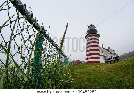 LUBEC-JULY 10: West Quody lighthouse in fogy day. The West Quoddy Head Light near Lubec, Maine, US is the eastern most point of the United States mainland. in Maine, USA on July 10, 2013.