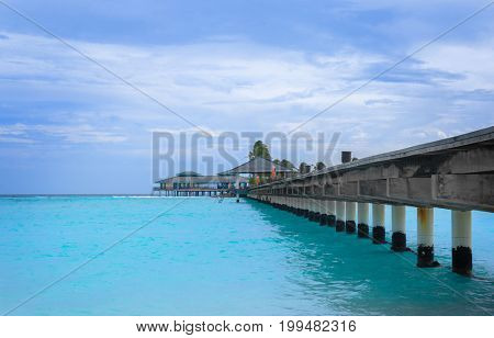 View of sea pontoon and bungalow at resort in summer day