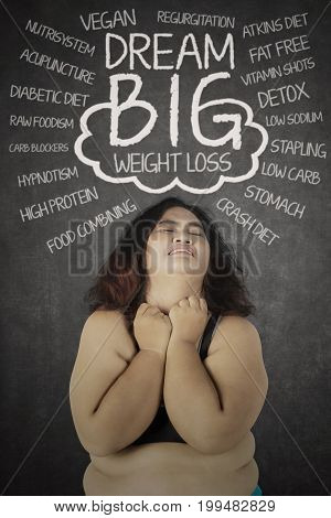 Portrait of overweight woman looks depressed while thinking her problems with text of dream big over her head