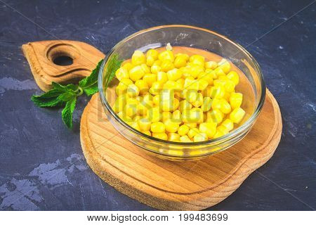 Canned Corn In A Glass Plate On A Gray Concrete Background.