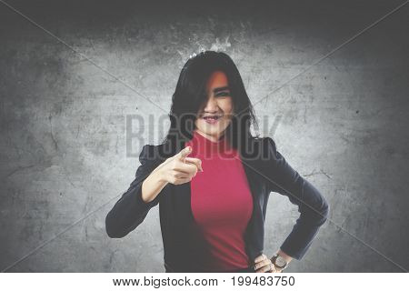 Image of Asian businesswoman looks stressful with smoke over her head while pointing at the camera