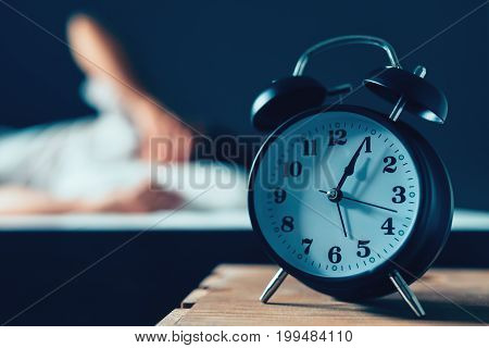 Sleeping disorder or insomnia concept selective focus of vintage clock in bedroom and out of focus male person trying to fall asleep in bed