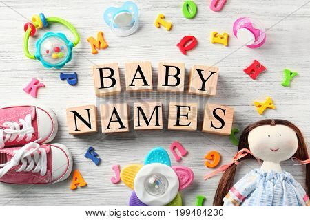 Cubes with text BABY NAMES, toys, pacifiers, plastic letters and shoes on wooden background