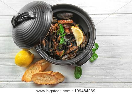 Pan with delicious mussels in tomato sauce on wooden table