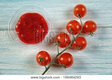 Tasty tomato sauce in plastic bowl on table