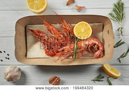 Cardboard box with delicious royal shrimps and lemon on table