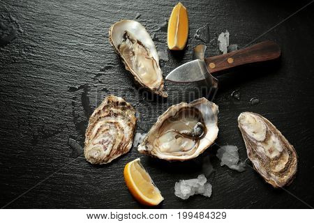 Delicious oysters with slices of lemon, knife and ice cubes on dark table
