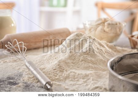 Heap of flour and whisk on kitchen table