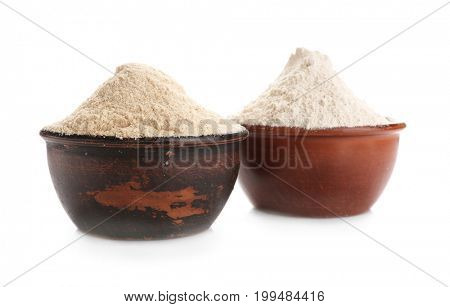 Bowls with oat and rye flour on white background