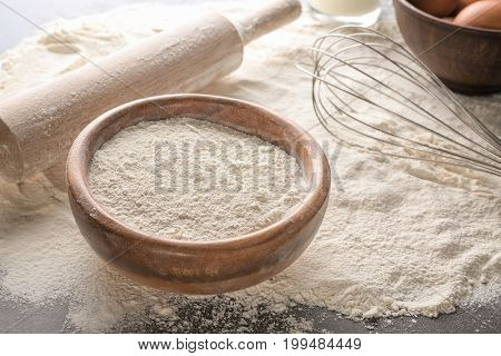 Bowl with white flour, rolling pin and whisk on kitchen table