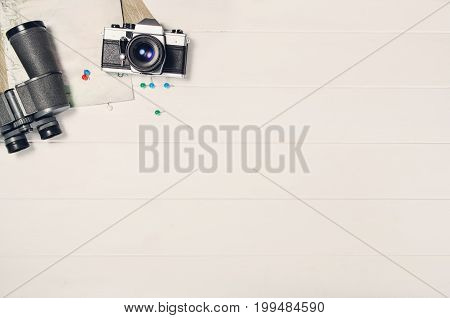 Accessories for travel top view on white wooden background with copy space. Adventure and wanderlust concept image with travel accessories. Preparing for an exotic trip, journey and sightseeing.
