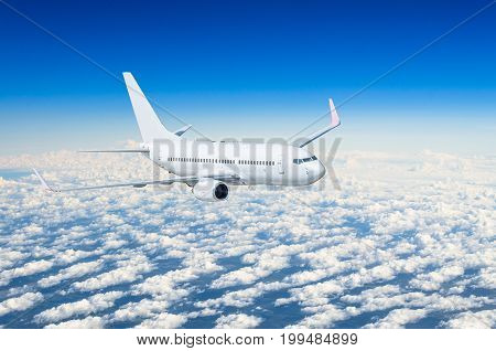 White Airplane Flies High In The Sky Above The Clouds Blue Sky