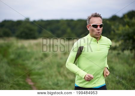 Healthy fit man wearing sunglasses jogging through rural grassland on a country track with copy space behind him on a blurred background in a close up upper body view