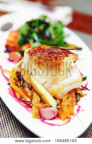 White fish fillet with vegetables, close-up, toned image