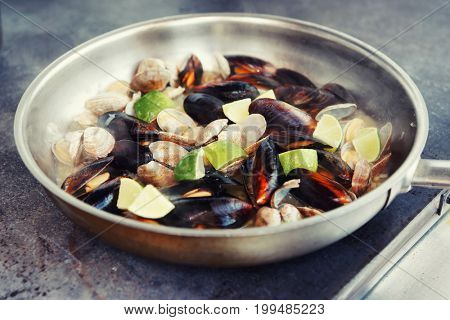 Clams and mussels fried with lime on hot pan at commercial kitchen, toned image