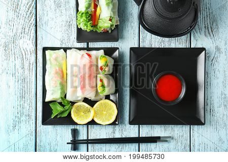 Portion of spring rolls on wooden background