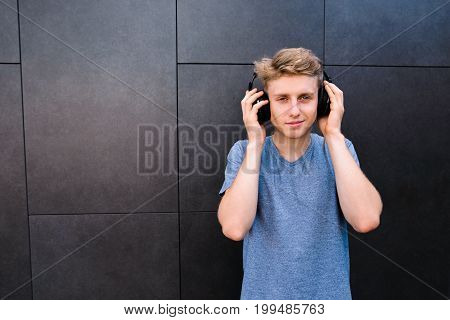 A smiling young man with his eyes closed listening to music in his headphones on the background of a gray wall. The teenager is enjoying listening to music.