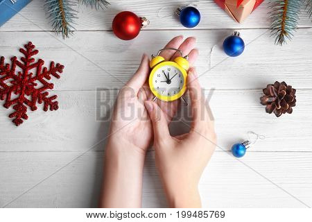 Woman holding retro alarm clock on wooden table. Christmas countdown concept
