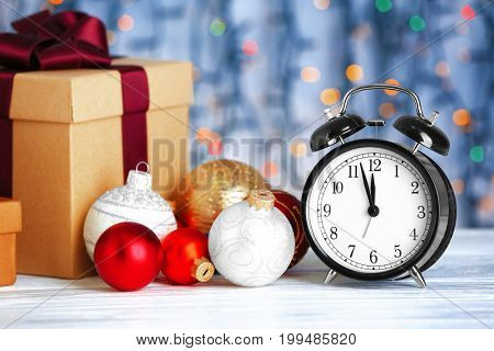 Retro alarm clock, decorations and gift box on wooden table. Christmas countdown concept