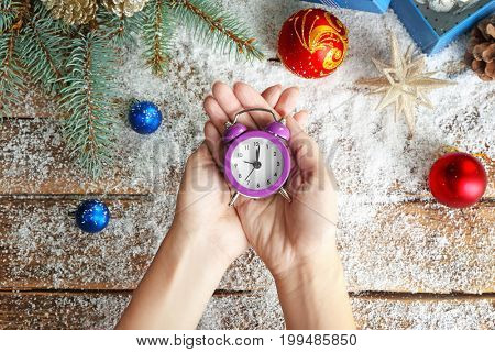 Woman holding retro alarm clock over table. Christmas countdown concept