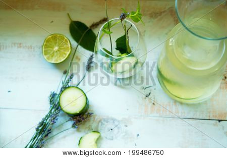Fresh Detox Infused Water with Cucumber Lime and Mint in glass bottle and glass with cut pieces of cucumber and lime on light blue wood background DIY healthy drink and juice conceptual background with healing lavender flowers and mint herbs ready to drin