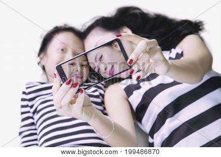 Image of a young mother with her daughter taking a selfie photo by using a smartphone while lying down on the studio