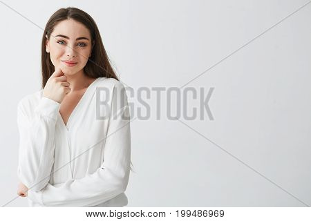 Portrait of young beautiful business lady looking at camera smiling touching face over white background. Copy space.
