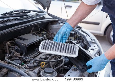 Internal combustion engine air filter. Auto mechanic wearing protective work gloves holding dirty air filter.