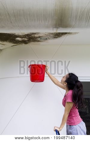 Image of young woman collecting drop rainwater from the damaged ceiling with a bucket