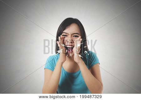 Young woman looks stressful shout and scream using her hands in front of camera