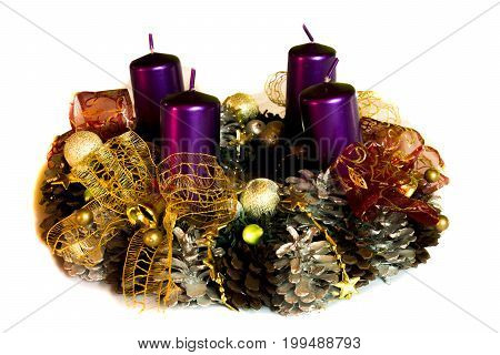 Advent wreath with four purple candles and Christmas decoration on clear white background.
