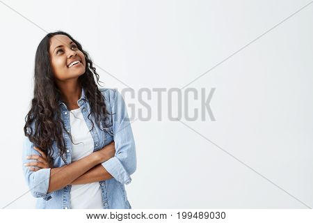 Pretty young Afro-American female brunette with long wavy hair looking up and away, sincerely smiling, keeping her arms folded on denim shirt. People and positive emotions concept.