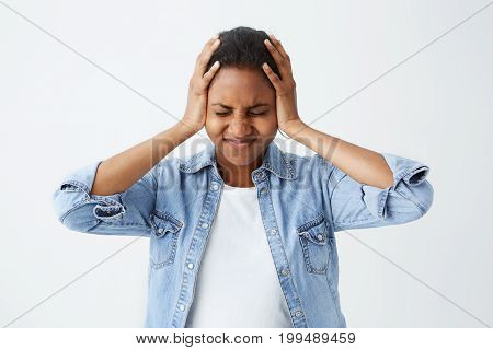 Photo of disappointed Afro-american woman in denim shirt holding her hands on temples frowning face and closed eyes in despair and terror. Woman regreting her act. Female in despair and shock