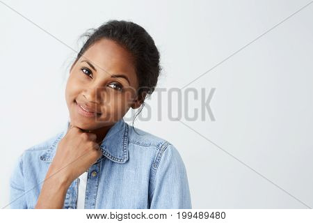 Close-up of Afro-American woman with dark warm eyes and appealing smile dressed in casual clothes posing on white background. Pretty dark-skinned woman having happy look isolated over white.