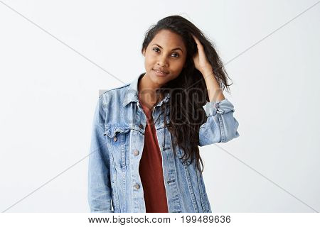Smiling young woman with dark wavy hair in denim jacket and red t-shirt, posing and playing with her hair. Afro-American girl dressed casually cheerfully looking at camera.