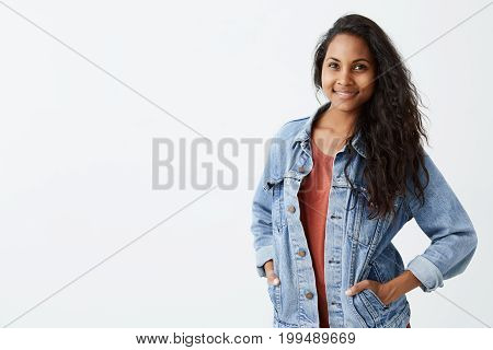 Cheerful gorgeous young woman with dark wavy hair wearing denim jacket in red t-shirt smiling pleasantly, standing with her hands in pockets. Pretty girl dressed in dressed casually looking at camera.