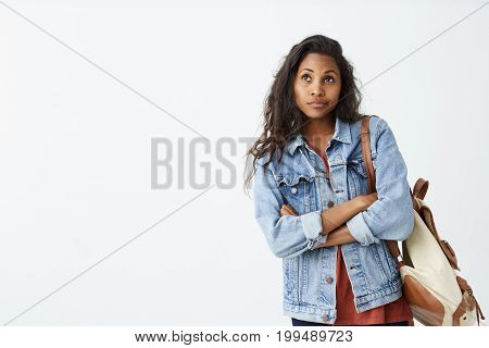 Indoor shot of cute dark-skinned girl looking away, having doubtful and indecisive face expression, pursuing her lips as if she is not satisfied. Confused young female in denim jacket with backpack posing isolated at white wall