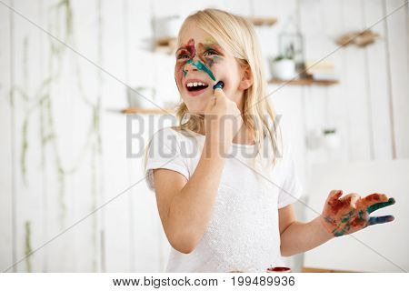 Playful seven-year-old blonde girl touching her face with finger in paint. Little girl painted her face with different colours. Playing kid.