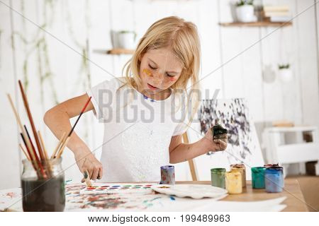 Creative beautiful female child with blonde hair workinh on her picture in the art room, Little blond standing behind desk with paint and palette, deeping her fingers in paint.