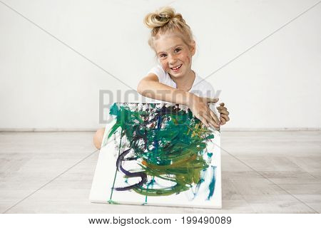Close-up portrait of blond European little girl with hair bun and freckles smiling with all her teeth. Holding on her knees picture that she painted for her parents, feeling proud of herself. People and positive emotions.