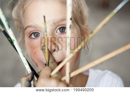 Headshot of adorable female blonde child, holding brushes in her hand, looking and smiling at the camera. Cute little girl with fair hair and blue eyes in white cloth. Happy childhood concept