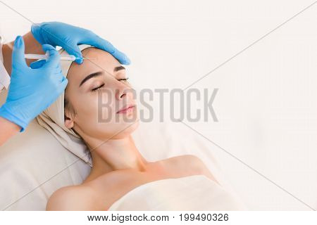 Young pretty woman receiving treatments in beauty salons. Young beautiful dark-haired woman in the office beautician lying on the couch. Beautiful woman face getting beauty injections