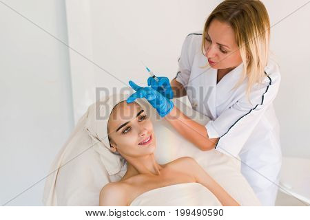 Young pretty woman receiving treatments in beauty salons. Young beautiful dark-haired woman in the office beautician lying on the couch. Contouring procedure revitalization. Beauty injections .