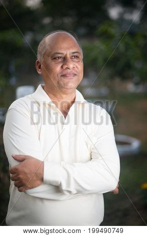 Confident mature businessman posing with arms crossed and looking at camera.