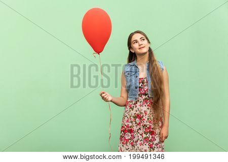 The beautiful blonde teenager dreaming with red ballon on a light green background. Isolated studio shot