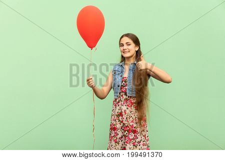 The beautiful blonde teenager with red ballons thumbs up and toothy smile on a green background. Isolated studio shot.