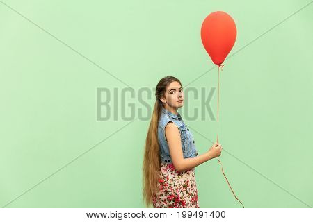 The beautiful blonde teenager looking at camera holding red balloon on a green background. Isolated studio shot